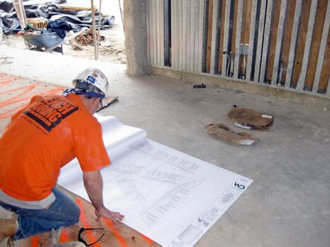 Constrution worker looking at blueprints for McBride High School