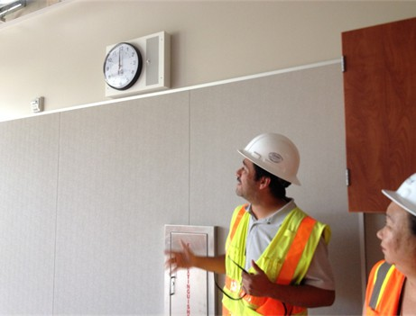 two construction workers looking at clock