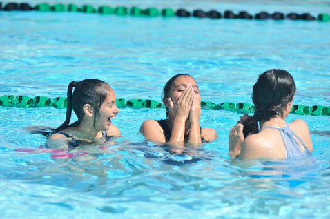 Three girls laughing in Cabrillo High School pool